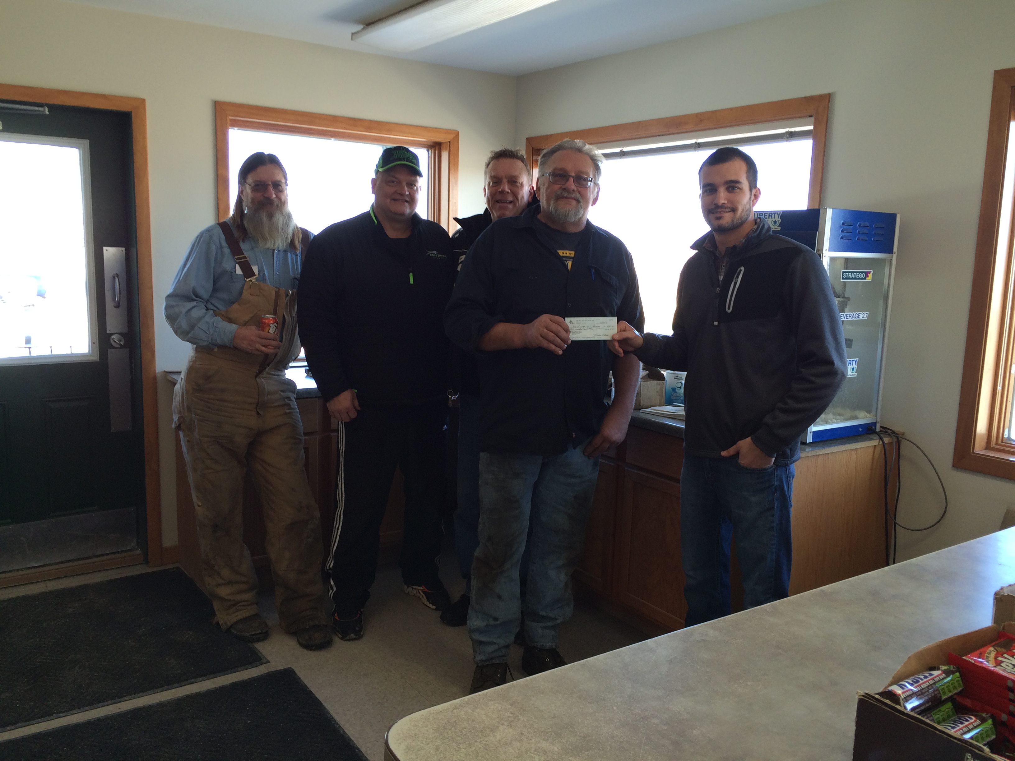 Brad Fabrizius, Kane County Corn Growers plot chairman, accepts a donation by the DeKane SnowTrackers snowmobile club